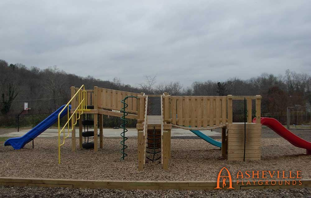 Playground with three slides and multiple platforms connected by bridges at the Asheville Christian Academy in Swannanoa, NC - Asheville Playgrounds