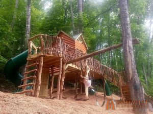 Log Cabin Playhouse On Hill with Swings, Ladder, Spiral Slide - Asheville Playgrounds