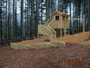 Wooden Playhouse on Hill with Retaining Wall, Slides, Swings, and Stairs - Asheville Playgrounds
